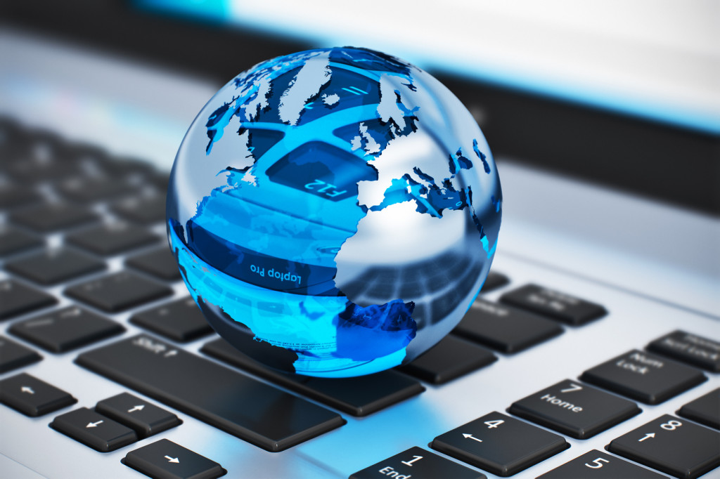 Creative abstract global communication and internet business telecommunication concept: macro view of crystal Earth globe on laptop or notebook keyboard with selective focus effect